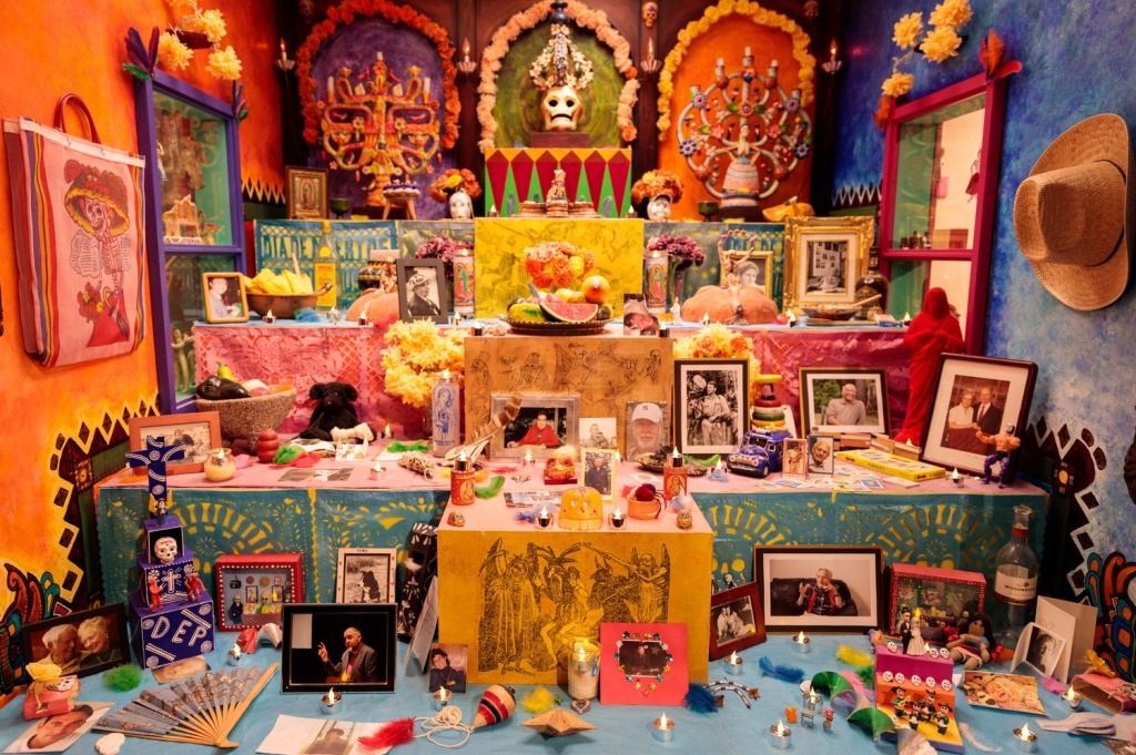 Photo of large, multi-tiered personal Dia de los Muertos altar decorated with photos of loved ones, skulls, candles, marigolds, food offerings, and many other objects.
