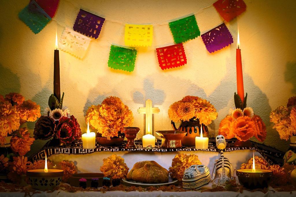 Dia de los Muertos altar with candles, bread, marigolds, and a flag banner
