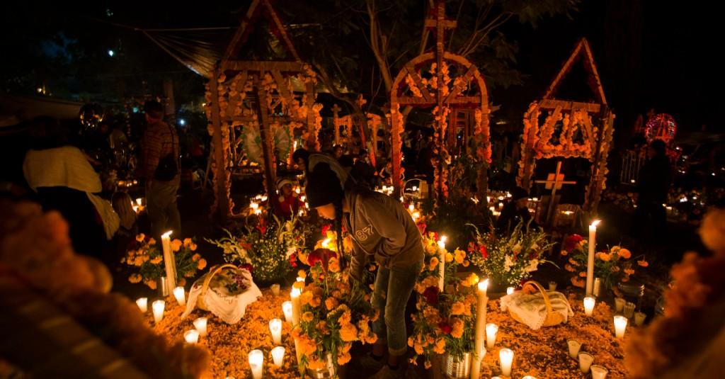 people visiting decorated graves for Dia de los Muertos