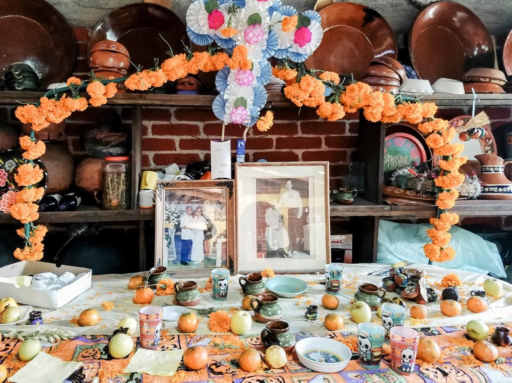 Photo of personal Dia de los Muertos altar with photos of deceased ancestors, fruit offerings, and marigolds